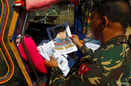 FILE - Soldiers distribute pictures of a member of extremist group Abu Sayyaf, Isnilon Hapilon, who has a U.S. government bounty of $5 million for his capture, in Butig, Lanao del Sur in southern Philippines, Feb. 1, 2017.