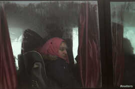 People evacuated from the two villages of Kefraya and al-Foua, after an agreement reached between rebels and Syria's army, ride a bus at insurgent-held al-Rashideen, Aleppo province, Syria, April 14, 2017.