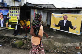 A woman walks in front a poster for Guinean presidential candidate, Alpha Conde, hung in front of the home of a supporter of his party (file photo)