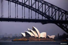 FILE - The sun illuminates the Sydney Opera House as a ferry sails past during a storm at Sydney Harbor in Australia.