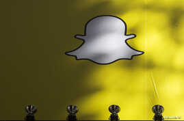FILE - A billboard displays the logo of Snapchat above Times Square in New York.