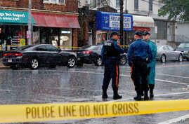 Police officers stand guard while law enforcement officers search an address during an investigation into Ahmad Khan Rahami, who was wanted for questioning in an explosion in New York, which authorities believe is linked to the explosive devices foun