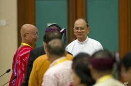 Myanmar President Thein Sein, rear right, shakes hands with leaders of armed ethnic groups during a meeting for the Nationwide Ceasefire Agreement (NCA) between representatives of the Myanmar government and leaders of armed ethnic groups in Naypyidaw