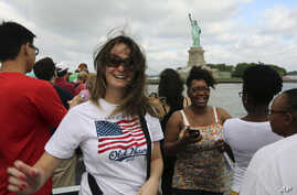 Visitors to the Statue of Liberty take photos as they arrive on the first tourist ferry to leave Manhattan, July 4, 2013 in New York.