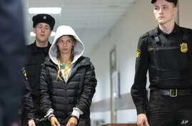 Anastasia Vashukevich, also known on social media as Nastya Rybka, center, is escorted in the court room in Moscow, Russia, Jan. 19, 2019.
