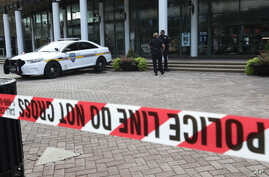 Jacksonville police officers guard an area, Aug. 27, 2018, near the scene of a fatal shooting at The Jacksonville Landing on Sunday in Jacksonville, Fla.
