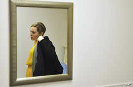 Heidi Wyandt, 27, puts on her coat to leave the Altoona Center for Clinical Research in Altoona, Pa., March 29, 2017, where she is helping test an experimental non-opioid pain medication for chronic back pain related to a work related injury she rece