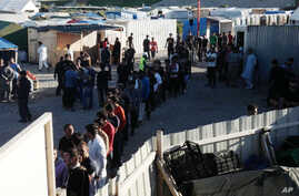 FILE- Migrants line up to receive their daily food distribution in a makeshift camp in Calais, northern France.