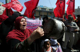 A Palestinian woman holds a cooking pot during a protest against a U.S. decision to cut funding to the U.N. Relief and Works Agency (UNRWA), outside an aid distribution center, in Khan Younis in the southern Gaza Strip, Sept. 4, 2018. On Sept. 8, the...