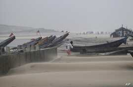 A fisherman walks near the anchored fishing boats as strong winds blow a day after a powerful cyclone pounded the Bay of Bengal coast in Gopalpur, Orissa, Oct. 13, 2014.