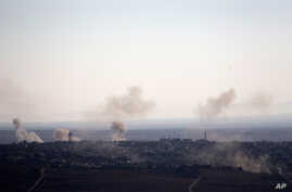 Smoke and explosions from the fighting between forces loyal to Syrian President Bashar Assad and rebels rise in the village of Jubata al-Khashab as seen from the Israeli-controlled Golan Heights, Sunday, Sept. 11, 2016.