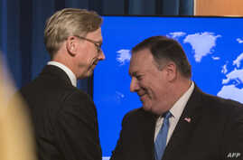 """FILE - The State Department's director of policy planning and head of the Iran Action Group, Brian Hook (L), shakes hands with Secretary of State Mike Pompeo after the announcement of the """"Iran Action Group"""", August 16, 2018."""