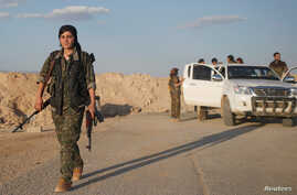 A female member of the Sinjar Resistance Units (YBS), a militia affiliated with the Kurdistan Workers' Party (PKK), carries a sniper and an AK-47 rifle in the village of Umm al-Dhiban, northern Iraq, April 29, 2016.