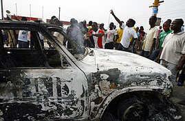 Ivorian students protest near a burnt U.N. vehicle during a demonstration at the junction of Riviera 2 in Abidjan, 13 Jan 2011