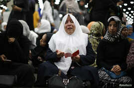Nahed Ahmed Zeead, 51, of Iraq, takes part in the jenazah, an Islamic funeral prayer, for the late boxing champion Muhammad Ali in Louisville, Kentucky, June 9, 2016.