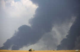Israeli tank sits in a field as heavy smoke rises from the Gaza Strip Tuesday, July 22, 2014. Israeli airstrikes pummeled a wide range of targets in the Gaza Strip on Tuesday as the U.N. chief and the U.S. secretary of state began an intensive effort...