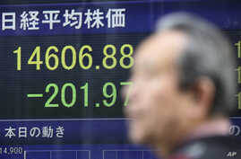 A man walks by an electronic stock price indicator showing the regional heavyweight, Tokyo's Nikkei 225, in Tokyo, April 8, 2014.