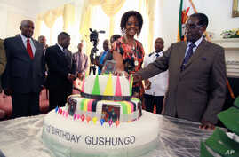 Zimbabwean President Robert Mugabe (R) and his wife Grace cut his birthday cake in Harare, Feb. 22, 2016. Staff in the President's office organized a surprise birthday celebration ahead of Saturday's birthday bash.