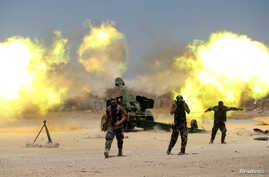 Shi'ite fighters with Iraqi security forces fire artillery during clashes with Islamic State militants near Falluja, Iraq, May 29, 2016.
