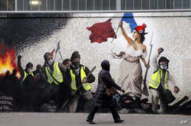 """A woman passes by a mural by street artist PBOY depicting Yellow Vest (gilets jaunes) protesters inspired by a painting by Eugene Delacroix, """"La Liberte guidant le Peuple"""" (Liberty Leading the People), in Paris, Jan. 10, 2019."""