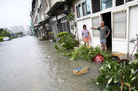 FILE - Local residents watch rising floodwaters from passing Tropical Storm Kong-Rey in Tainan, Taiwan.
