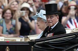 FILE - In this June 17, 2017 file photo, Britain's Queen Elizabeth II and Prince Philip return to Buckingham Palace in a carriage, after attending the annual Trooping the Colour Ceremony in London.