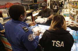 Chef Creole owner Wilkinson Sejour hands out free hot meals to TSA workers at his restaurant at Miami International Airport, Jan. 15, 2019, in Miami.