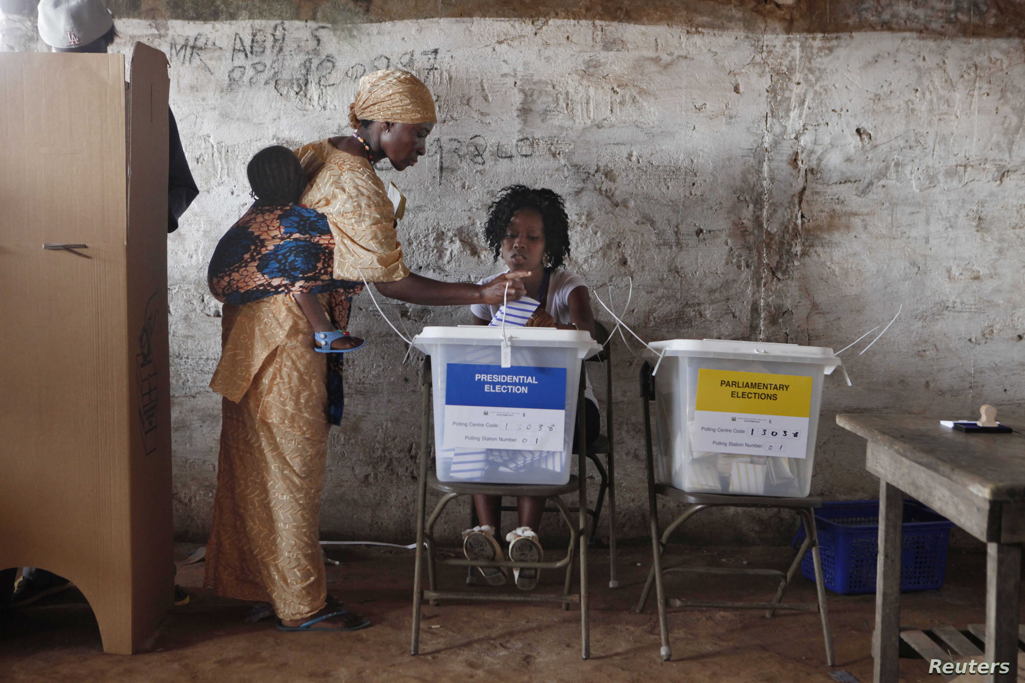 A woman carrying a baby on her back votes in Freetown November 17, 2012.