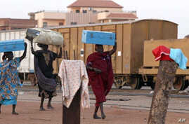 Southern Sudanese women carry their luggage as they prepare to board a train in Khartoum on January 9, 2011 on their way to the south