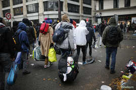 Migrants carry their belongings as they wait before entering buses as part of their transfer by French authorities to reception centers across the country during the dismantlement of makeshift camps in a street near Stalingrad metro station in Paris,
