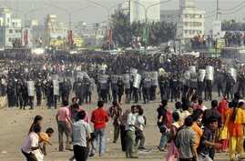 Protesting Bangladeshi garment workers throw stones at police near the international airport in Dhaka, Bangladesh, Sunday, Dec. 12, 2010. They were demanding the implementation of a new minimum wage.