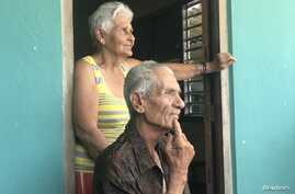 Miguel Barroz Lozano, 82, sits with his wife on the front porch of their farm house in rural Matanzas Province, Cuba, July 9, 2018.