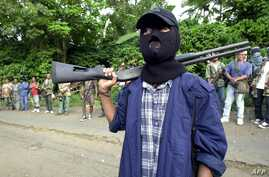 FILE - A masked Abu Sayyaf gunman and other rebels gather outside a mosque in Bandang in Jolo island, May 27, 2000.