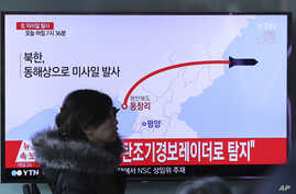 A woman at a train station in Seoul walks by a TV screen showing a news report about North Korea's missile test, March 6, 2017.