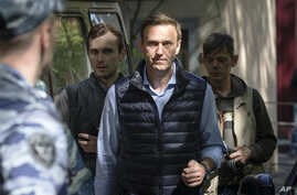 FILE - Russian opposition leader Alexei Navalny, center, arrives at court after his arrest during a protest in Moscow, Russia, May 11, 2018.