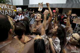 Environmental activists chant slogans during a protest in front of the headquarters of Brazilian mining company Vale SA in downtown Rio de Janeiro, Nov. 16, 2015.
