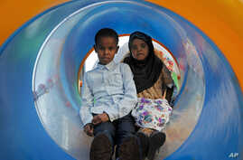 In this photo taken Sunday, Aug. 21, 2016, Somali children play at the Peace Garden public park in Mogadishu, Somalia. War-weary Somalis are trying to relax and rebuild their country after decades of violence, but the homegrown Islamic extremists al-