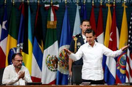 Mexico's President Enrique Pena Nieto greets the audience next to Mexico's Foreign Minister Luis Videgaray during the opening ceremony of OAS 47th General Assembly in Cancun, Mexico, June 19, 2017.