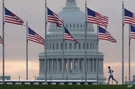 FILE - An early morning runner crosses in front of the U.S. Capitol as he passes the flags circling the Washington Monument in Washington, Sept. 27, 2017.