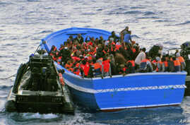 In this photo released by the Italian Navy on May 22, 2014, a fishing boat filled with migrants receives aid from an Italian Navy motor boat.