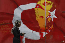 A woman walks past a billboard with a Turkish flag decorated with an image of Turkey's founder Kemal Ataturk, in Istanbul, April 12, 2017.