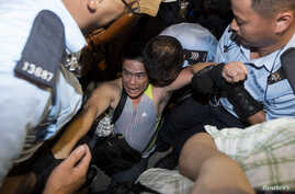 A protester is taken away by police officers after staying overnight at Hong Kong's financial Central district, July 2, 2014.