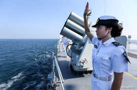 FILE - A Chinese soldier waves farewell to Russian fleets as the Chinese-Russian joint naval drill concludes in Zhanjiang, Guangdong Province, China.