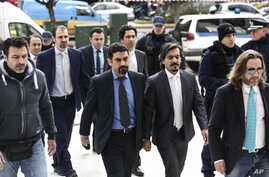 Turkish military officers, center, escorted by Greek police officers, arrive at the Supreme Court in Athens, Jan. 26, 2017. A group of Turkish servicemen who fled to Greece in a military helicopter after last year's failed coup have appeared at Greec