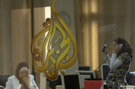 FILE - The Al Jazeera logo is seen through a window at the offices of the Arabic news channel in Ramallah, West Bank, July 15, 2009.