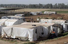 Syrian refugees walk outside their tents at a Syrian refugee camp in the eastern Lebanese town of Majdal Anjar, Lebanon, June 19, 2014.