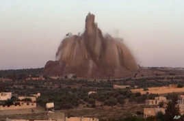 FILE - This file image made from video posted May 14, 2014, by Shaam News Network (SNN), an anti-Bashar Assad activist group, which has been verified and is consistent with other AP reporting, shows the bombing of a large amount of explosives in a tu