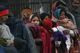 FILE - Indian homeless people wait for free food outside a temple, in New Delhi, India, Jan. 1, 2013.