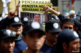 A protester holds a banner outside a court during the first day of the blasphemy trial of Jakarta's Governor Basuki Tjahaja Purnama, also known as Ahok, in Jakarta, Indonesia December 13, 2016.