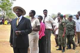 Uganda's President Yoweri Kaguta Museveni, wearing hat at left,  stands in a queue as he waits with other voters to place his ballot in Kiruhura district, which is Museveni's home area, at a Polling station about 300 Kms (200 miles) west of Kampala,
